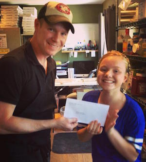 Gordon Fletcher gives his daughter Kameela her first paycheck